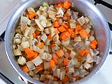 鍋に、オリーブオイルと野菜を入れ、しんなりするまで炒める。ベーコンを加え、さらに炒める。