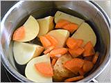 鍋に新じゃがいもとにんじんを入れ、ひたひたの水を加えて火にかけ、火が通ったら湯を捨てて、新じゃがいもは皮をむいて軽くつぶす。