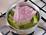 鍋に長ネギを入れ、かぶるくらいの水、ベーコン、ローリエを入れて火にかける。沸騰したら、ふたをして弱火で2、3分煮て、十分柔らかくなったらふたを開け、さらに水分がなくなるまで煮る。