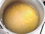 水とコンソメを入れ、強火にする。沸騰したら弱火にする。4~5分経ったところでグリンピースを加える。
